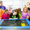 YMCA of Southern Indiana Floyd County Branch summer campers watch the operation of a laser machine in the Manufacturing Lab at the Purdue University College of Technology in New Albany on Thursday morning. Staff photo by Christopher Fryer