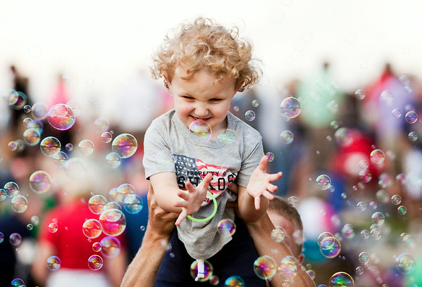 Sutton Turnage, 2, New Albany, pops bubbles during the Independence Day Celebration at the New Albany Riverfront Amphitheater on Thursday evening. Staff photo by Christopher Fryer