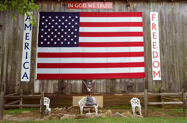 "An American flag hangs from Charles Jones's barn in Charlestown Wednesday morning. Jones, a Vietnam veteran, said he has displayed the flag for the past 5 years ""in rememberance and honor for all Americans, and the heroes we left behind."" Jones, who has lived in Charlestown for the past 65 years, found help from family and friends in mounting the 12 x 15 foot flag.<br /> Staff photo by Tyler Stewart"