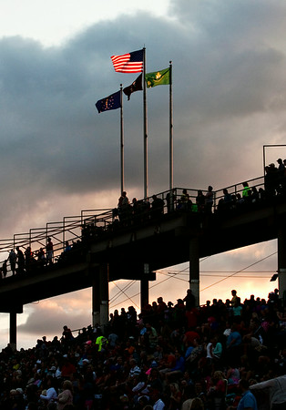 An American flag is illuminated above the crowd while the Louisville Crashers perform during the Independence Day Celebration at the New Albany Riverfront Amphitheater on Thursday evening. Staff photo by Christopher Fryer
