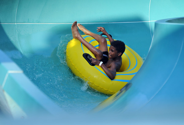 K.D. Powell, 10, carves around a corner on the Clarksville Family Aquatic Center slide as part of the Family Campout Day in Colgate Park Saturday evening. For $10, each family set up a tent, enjoyed free activities and had exclusive after hour access to the aquatic center.<br /> Staff photo by Tyler Stewart