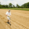 Paul Bierman, Floyds Knobs, plants pumpkin seeds in a field on his father's farm at the corner of Balmer-Fenwick and Banet roads in Floyd County on Friday afternoon. He plans to sell the crop for jack-o-lanterns in the fall, and use the profits to help put his daughter through Indiana University Southeast. He and his wife also plan to use the pumpkin patch as a set in children's photos for their business, Bierman Photography. Staff photo by Christopher Fryer