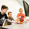 From left, Porter Gohmann, 11, New Albany, Seth Young, 10, Memphis, and Fletcher Gohmann, 8, New Albany, use software to program a kicker robot in the LEGO robotics course at Ivy Tech's Kids' College in Sellersburg on Monday morning. Staff photo by Christopher Fryer