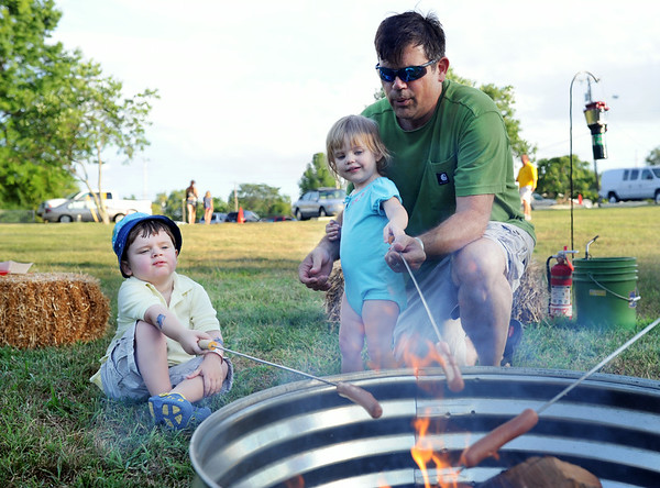 Tony Kaelin, Greenville roasts a hot dog with daughter Izzy, 2, and Will, 3, at the Clarksville Family Campout at Colgate Park Saturday evening. For the first time ever, families were allowed to set up camp in Colgate park for $10 per family, where they enjoyed free activities and exclusive after hour access to the Clarksville Family Aquatic Center.<br /> Staff photo by Tyler Stewart