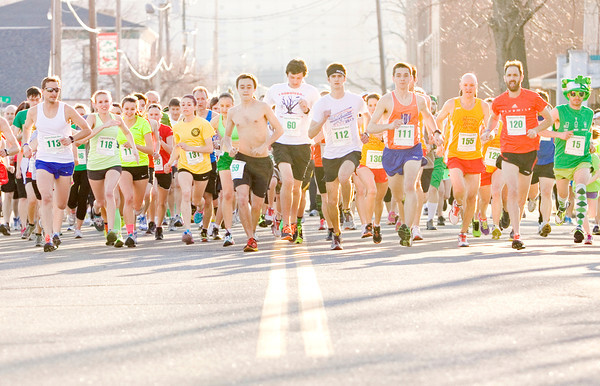 Participants leave the start line at the beginning of the sixth annual Leprechaun Run along Chestnut Street in Jeffersonville on Tuesday evening. More than 150 people took part in the two-mile race. Staff photo by Christopher Fryer