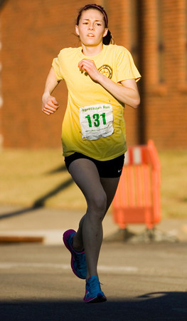 Cia Greene, 15, Henryville, approaches the finish line during the sixth annual Leprechaun Run along Chestnut Street in Jeffersonville on Tuesday evening. Greene broke the previous women's record of 12:27 with a time of 11:49. Staff photo by Christopher Fryer