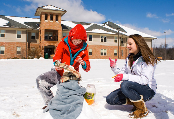 Indiana University Southeast freshmen Justine Staggs, Santa Claus, left, and Jayme Lindauer, St. Henry, put the finishing touches on a snowman they built on campus Monday afternoon in New Albany. According to the National Weather Service, Tuesday will have a high near 33 with possible windchill values in the single digits. Staff photo by Christopher Fryer