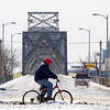 A cyclist moves through the intersection of U.S. 31 and Court Avenue near the Clark Memorial Bridge in Jeffersonville on Monday afternoon. The Indiana approach to the bridge will be reduced to two lanes and sidewalk access will be closed beginning March 10 for crews to dismantle the two historic pylons and railings on the Indiana side of the bridge. Staff photo by Christopher Fryer