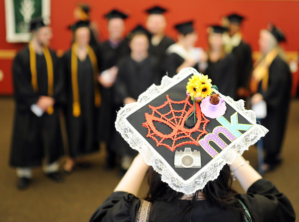 Morgan Krupski, New Albany, takes a photo of her fellow classmates of the School of Fine Arts & Design during Ivy Tech's 2014 graduation ceremony at Northside Christian Church Tuesday.<br /> Staff photo by Tyler Stewart