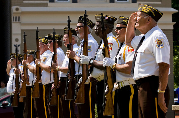 Members from Veterans of Foreign Wars posts 1693 and 3281 look on as a bugler plays taps during the annual Memorial Day service at Veterans Plaza in New Albany on Monday morning. Staff photo by Christopher Fryer