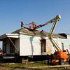 A crew with Blocker Construction, out of New Albany, works to remove part of the roof on a historic home at the corner of Pearl and Market streets so the structure can be hauled underneath the Indiana approach to the Big Four Bridge and moved down Mulberry Street to a lot at the corner of Pearl and Maple streets in Jeffersonville on Thursday morning. Staff photo by Christopher Fryer