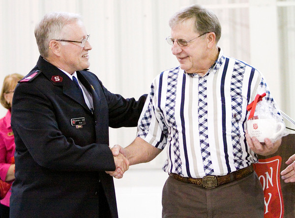 Danny Downs, New Albany, right, shakes hands with Corps Officer Maj. Stephen Kiger while being recognized for his volunteer service during The Salvation Army Southern Indiana's annual volunteer luncheon in New Albany on Wednesday. Staff photo by Christopher Fryer