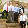 From left, Edwin Coots IV, Joseph Leach, Edwin Coots V, and Charles Whittaker, stand next to the recently refurbished clock on the side of E.M. Coots' Sons Funeral Home in Jeffersonville on Thursday afternoon. The clock has been on the business since the 1940s, and the owners had the exterior painted, the neon restored and the clockworks tuned up. Staff photo by Christopher Fryer