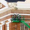 A crew with Resch Construction works on the capitals and cornices on the Town Clock Church along Main Street in New Albany. Staff photo by Christopher Fryer