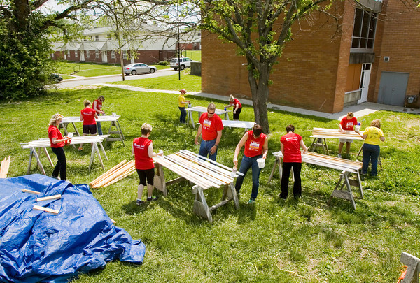 Realtors with Semonin Realtors prime trim at a staging area along Dennison Avenue as part of Habitat for Humanity's National Women Build Week in New Albany on Thursday afternoon. The trim will be used for a project on Culbertson Avenue. Staff photo by Christopher Fryer