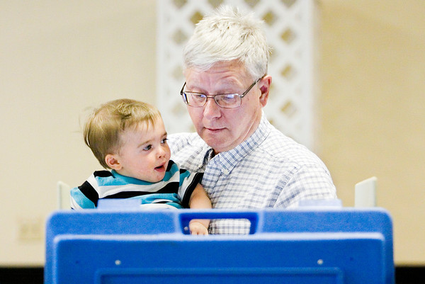 Eddie Freiberger holds his grandson, Camden Meyer, 1, both of New Albany, while he uses an electronic voting machine to fill out his ballot at Newlin Hall in New Albany on Tuesday afternoon. Staff photo by Christopher Fryer