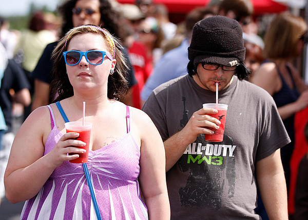 Tiffany Carroll and Joshua Faucette cool down with strawberry smoothies at the St. John's Starlight Strawberry Festival. Organizers said pleasant weather probably contributed to bigger-than-expected crowds. Staff photo by Jerod Clapp