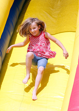 Jenah Jones bounces down an inflatable slide at St. John's Starlight Strawberry Festival. Inflatable rides and other attractions entertained children. Staff photo by Jerod Clapp