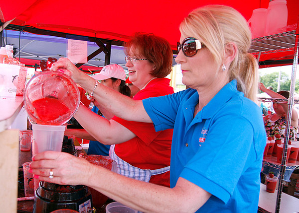 Paula Zurschmiede and Nina Fulda-Portman make strawberry smoothies in a hurry at the St. John's Starlight Strawberry Festival on Saturday. The smoothie station was one of the first stops for guests as they made their way in. Staff photo by Jerod Clapp