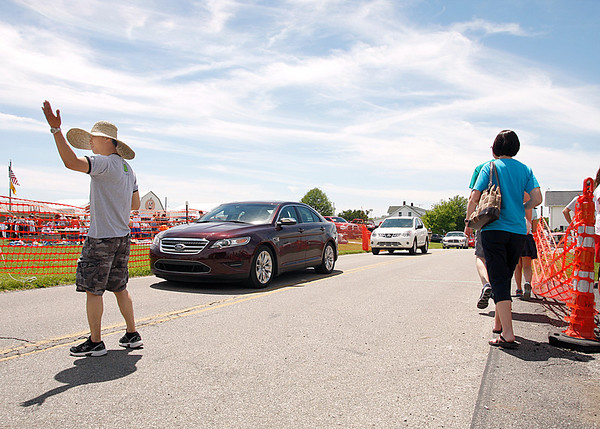 Michael Lamsfuss, a volunteer for St. John Starlight, directs traffic and pedestrians for the annual Strawberry Festival. Parking got scarce quickly. Staff photo by Jerod Clapp