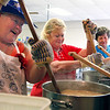 Ginny Balmer, Jackie Colin and Betty Kruer stir pots of chicken and dumplings for the crowd at the St. John Starlight Strawberry Festival on Saturday. Balmer said they were working on a batch that would make their 195th gallon of the day with another four hours to go. Staff photo by Jerod Clapp