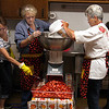 Sue Harpe, Paulette Kruer and Hilda Schmidt run one of many batches of strawberries through a slicer on Saturday. Among strawberry shortcakes, smoothies and other treats, volunteers didn't stop prepping and serving up the berries. Staff photo by Jerod Clapp