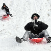 James Reed, 12, races against his mother, Darby, race down the flood wall hill along Riverside Drive in Clarksville on Tuesday afternoon following roughly 8 inches of snow in the area. The Reed family has been traveling from Sellersburg and sledding on the flood wall for the past nine years. <br /> Staff photo by Tyler Stewart