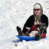 Alexus Owens, 18, holds tightly on to her three-month-old pit bull puppy, Scarlet, as they barrel down the flood wall together on a sled Tuesday afternoon in Clarksville. <br /> Staff photo by Tyler Stewart