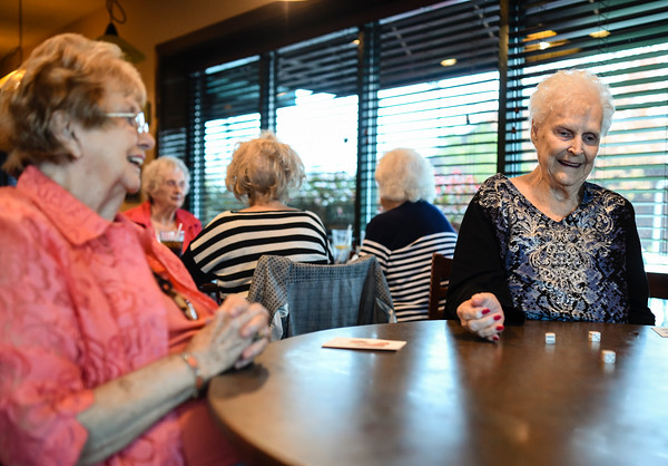 Liz Jenkins, 81, New Albany, rolls the dice during a game of bunco as fellow member Norma Whitaker, left, laughs with the group while at O'Charleys in Clarksville on Wednesday afternoon. The bunco club, a group of eight women which gather monthly, have been playing for nearly 58 years. Staff photo by Tyler Stewart