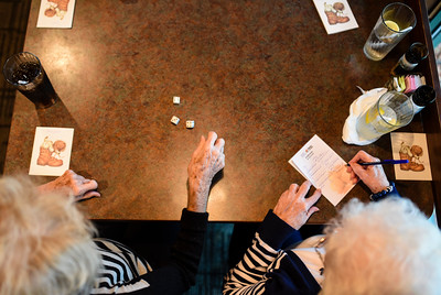 """Margaret Henninger, 88, throws the dice during a round of bunco as Norma Keller, 88, tallies numbers as part of the Bunco Club's monthly meeting at O'Charleys in Clarksville on Wednesday afternoon. The club, which has been meeting for nearly 58 years, keeps the focus on friendship and socialization. """"We've been friends since the first grade,"""" said Keller about Henninger. """"She was even in my wedding."""" Staff photo by Tyler Stewart"""