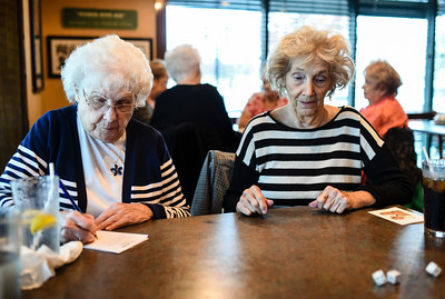 Bunco club member Margaret Henninger, 88, waits for the dice to settle after her throw as Norma Keller, 88, tallies the scores during the club's monthly meeting at O'Charleys in Clarksville on Wednesday afternoon. Timberlake has played with the club for nearly 58 years, and Henninger has played for the past 15. Staff photo by Tyler Stewart