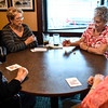 Edna Beets, 81, New Albany, takes her turn at rolling the dice as fellow Bunco club members Sue Bobo, 75, left-center, Liz Jenkins, 81, left, and Norma Whitaker, 88, right, wait for the results during the club's monthly meeting at O'Charleys in Clarksville on Wednesday afternoon. Staff photo by Tyler Stewart
