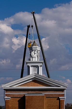 Crews with D&M Masonry and Padgett Inc. work to remove the steeple from the clock tower of the Second Baptist Church in downtown New Albany on Friday morning. The structure was removed to place steel bracing in preparation for a new steeple that will be installed late next month. Staff photo by Christopher Fryer