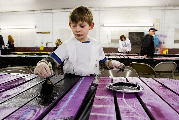 LeoKnight Wenglikowski, 6, paints one of the 96 panels made from 1,728 hand-sanded boards that will be used in an outdoor art installation in the downtown area during a Jeffersonville Arts Movement community art session Saturday morning. More than 100 people participated in the JAM session that was put on by the Jeffersonville Arts Alliance and the Jeffersonville Public Art Commission, and the site, which is the former Gray and Wells body shop, was provided by the Jeffersonville Redevelopment Commission. Staff photo by Christopher Fryer