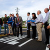 Clarksville Town Council President Paul Fetter, center, cuts the ribbon during a ceremony opening a 800-foot Court Avenue extension to extend the roadway to Woerner Avenue in Clarksville on Monday morning. Staff photo by Christopher Fryer