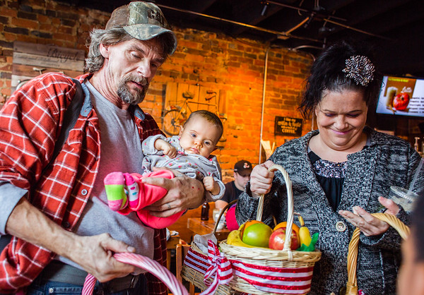 (left to right) Dale Brown, his three-month-old daughter Danika, and Emily Sterrett pick up baskets of fruit at Two Tired Bike & Bean to take back to Haven House on Thursday. Staff Photo By Josh Hicks