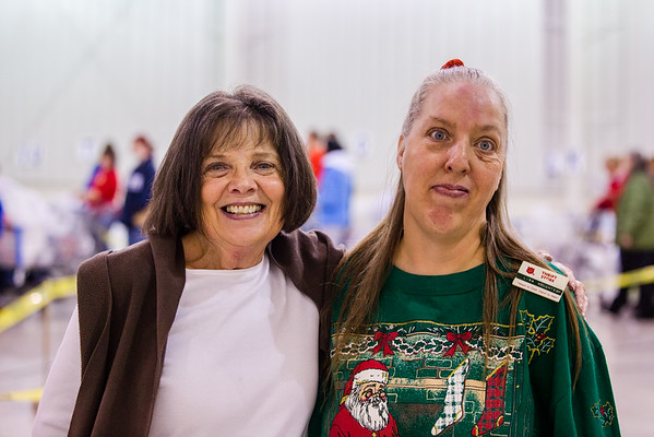 Susan Hawkins, left, spends her first volunteer experience at the Salvation Army alongside 20-year veteran Lisa Wright during their Angel Tree event on Saturday. Staff Photo By Josh Hicks