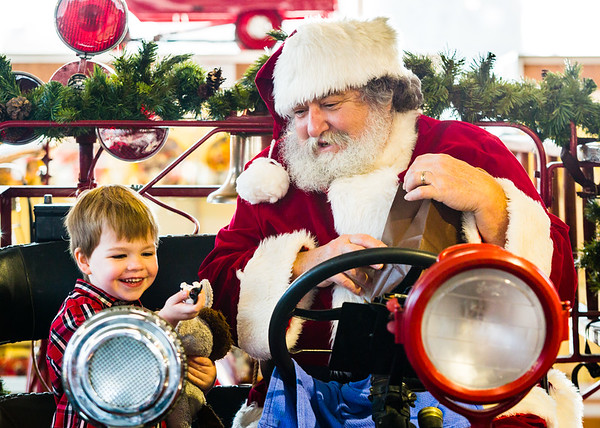 Santa delivers a toy dalmatian to Harrison Catt, 3, during Snacks with Santa at the Vintage Firefighter Museum in Jeffersonville on Saturday. Staff Photo By Josh Hicks