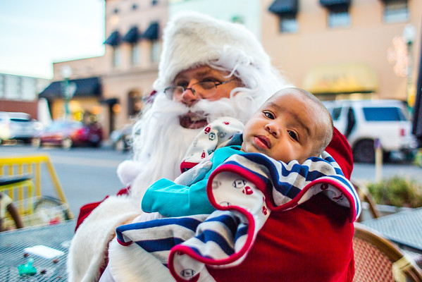 Santa cradles four-month-old Andres Cintron outside Two Tired Bike & Bean after Haven House families visited the coffee shop to receive Christmas presents and snacks on Thursday. Staff Photo By Josh Hicks
