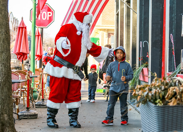 Josiah Swearingen, 7, walks with Santa down Spring Street in Jeffersonville, on their way to Two Tired Bike & Bean on Thursday. Haven House Families gathered at the coffee shop on Thursday to receive gifts sponsored by Two Tired Bike & Bean and Red Yeti. Staff Photo By Josh Hicks