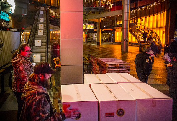 Volunteers go up to Tengo Sed Cantina at 4th Street Live! to box up Christmas meals for military families in Kentucky and Southern Indiana. The boxed meals then travel down an escalator to be distributed to several vehicles. Staff Photo By Josh Hicks