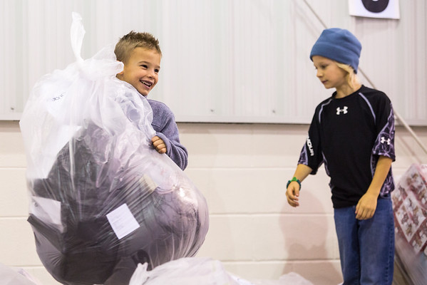 Seven-year-old Wyland McCormick, left, and his brother Paxton, 9, have volunteered at the Salvation Army for three to four years. The bag Wyland holds contains clothing picked out for a specific family, who will pick it up as they move through the long line at the Salvation Army Angel Tree event on Saturday. Staff Photo By Josh Hicks