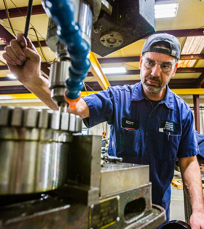 Machinist Scott Harden uses a mill to bore a hole into a gear at Spencer Machine & Tool. Harden has worked for the company for five years. Staff Photo By Josh Hicks