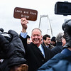 Jeffersonville Mayor Mike Moore raises a souvenir sign with the east end bridge's new title, the Lewis and Clark Bridge, following the opening ceremony on Sunday. Staff photo by Tyler Stewart