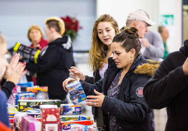 Melissa Warren, right, looks for toys for her seven and nine-year-old sons with the help of first time volunteer Jeannine Barr at the Salvation Army on Saturday during their Angel Tree event. Staff Photo By Josh Hicks