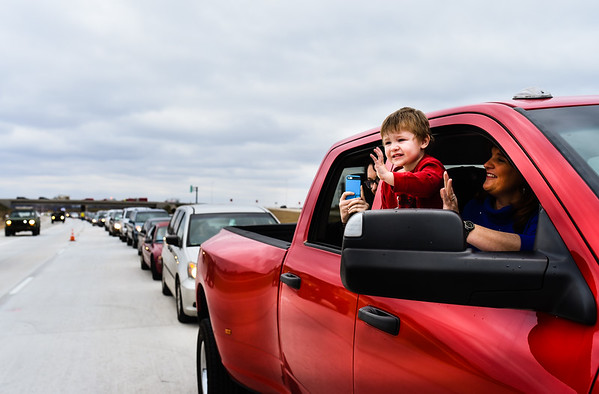 Daniel Wheeler, 3, Jeffersonville, waves to the passing military convoy as he and his family wait as the first in line for the opening of the Lewis and Clark Bridge on Sunday. Staff photo by Tyler Stewart