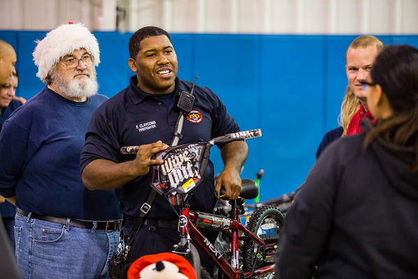 Trey Claycomb, member of the New Albany Fire Department, hands over a bicycle to Melinda Flores, whose son is six-years-old, at the Salvation Army's Angel Tree event on Saturday. Staff Photo By Josh Hicks