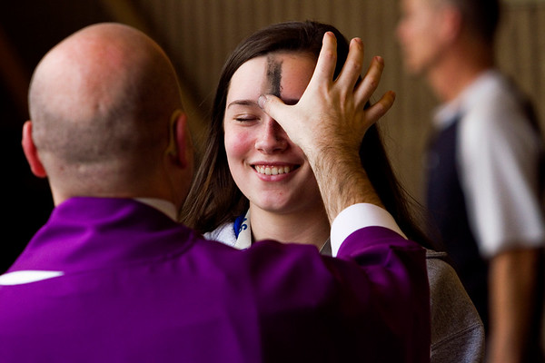 Rev. Adam Ahern applies ashes to senior Anna Wingate's forehead during the Ash Wednesday service in the auditorium at Our Lady of Providence Junior-Senior High School in Clarksville last week. Staff photo by Christopher Fryer