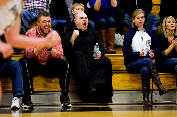 Rev. Adam Ahern cheers on the Our Lady of Providence Junior-Senior High School varsity girls basketball team during the Pioneers' 59-40 win over Paoli High School in the Class 2A Henryville Sectional tournament earlier this month. Rev. Ahern started serving as Providence's chaplain last fall after being ordained in the Catholic priesthood last June. Staff photo by Christopher Fryer