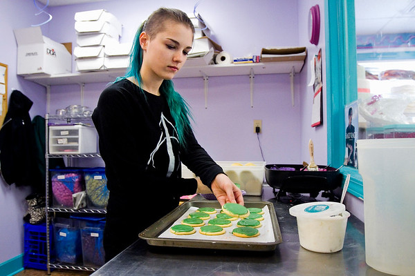 """Decorator Lindsey Krowiarz, New Albany, places a Mardi Gras cookie on a pan after applying white-chocolate icing at Sweet Stuff Bakery in downtown New Albany in preparation for """"Fat Tuesday"""" business Monday afternoon. Staff photo by Christopher Fryer"""